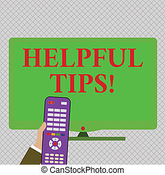 Conceptual hand writing showing Helpful Tips. Business photo text secret information or advice given to be helpful knowledge Hand Holding Remote Control infront of Wide Color PC Screen.