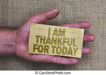 Conceptual hand writing showing I Am Thankful For Today. Business photo showcasing Grateful about living one more day Philosophy Thick gray paper with words human hands jute sack background.