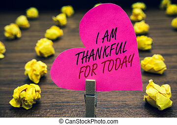 Conceptual hand writing showing I Am Thankful For Today. Business photo text Grateful about living one more day Philosophy Paperclip hold pink written heart woody floor with yellow lobs.