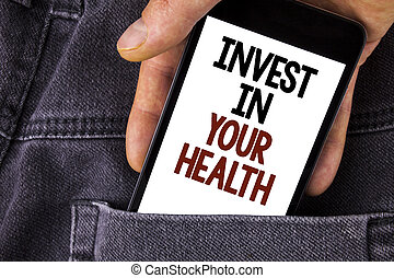 Conceptual hand writing showing Invest In Your Health. Business photo text Spend money in personal healthcare Preventive Tests written on Mobile Phone holding by man on the Jeans background.
