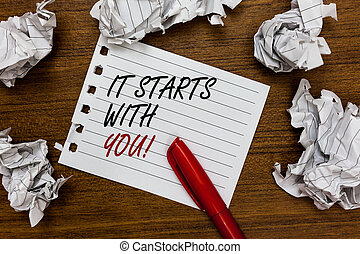Conceptual hand writing showing It Starts With You. Business photo showcasing Motivation for starting doing something Have discipline Written white page touched red marker scattered paper lump.