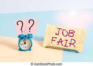 Conceptual hand writing showing Job Fair. Business photo showcasing event in which employers recruiters give information to employees Alarm clock beside a Paper sheet placed on pastel backdrop.