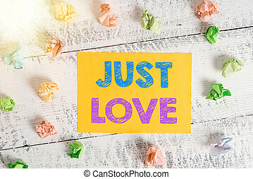 Conceptual hand writing showing Just Love. Business photo showcasing being interested physically in someone An emotional attachment Crumpled rectangle squared paper reminder white wood desk.