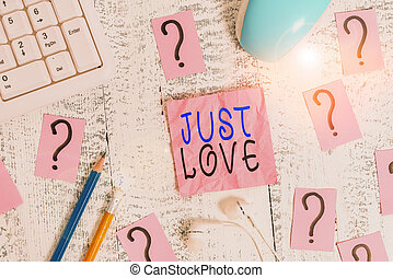 Conceptual hand writing showing Just Love. Business photo text being interested physically in someone An emotional attachment Writing tools and scribbled paper on top of the wooden table.