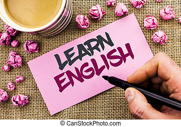 Conceptual hand writing showing Learn English. Business photo text Study another Language Learn Something Foreign Communication written by Man Holding Marker on Paper on the jute background Cup