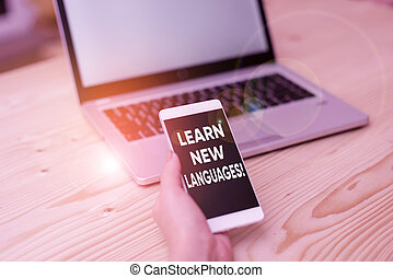 Conceptual hand writing showing Learn New Languages. Business photo showcasing developing ability to communicate in foreign lang woman with laptop smartphone and office supplies technology.