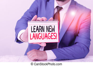 Conceptual hand writing showing Learn New Languages. Business photo showcasing developing ability to communicate in foreign lang Man holds empty paper with copy space in front of him Space.