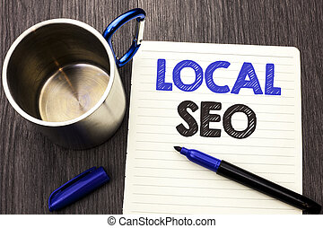 Conceptual hand writing showing Local Seo. Business photo showcasing Search Engine Optimization Strategy Optimize Local Find Keywords written on Notebook Paper wooden background Marker and Cup