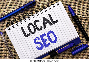 Conceptual hand writing showing Local Seo. Business photo showcasing Search Engine Optimization Strategy Optimize Local Find Keywords written on Notebook Book on jute background Pens next to it.