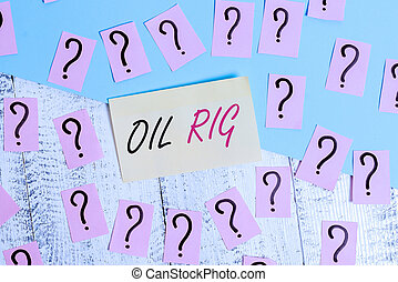 Conceptual hand writing showing Oil Rig. Business photo text large structure with equipment to remove oil from under the seabed Crumbling papers with thick cardboard on the wooden table.