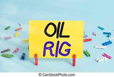Conceptual hand writing showing Oil Rig. Business photo text large structure with equipment to remove oil from under the seabed Colored clothespin rectangle shaped paper blue background.