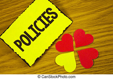 Conceptual hand writing showing Policies. Business photo text Business Company or Government Rules Regulations Standards written on Sticky note paper on wooden background Paper Love Hearts