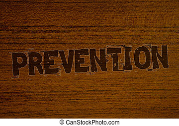 Conceptual hand writing showing Prevention. Business photos showcasing Stopping something from happening Healthcare ProtectionBold brown letters words ideas on wooden background concept messages.