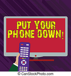 Conceptual hand writing showing Put Your Phone Down. Business photo text end telephone connection saying goodbye caller Hand Holding Remote Control infront of Wide Color PC Screen.
