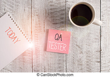 Conceptual hand writing showing Qa Tester. Concept meaning Quality assurance of an on going project before implementation Stationary placed next to a coffee cup above wooden table
