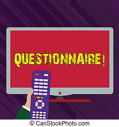 Conceptual hand writing showing Questionnaire. Business photo text Questions with a choice of answers Survey Statistical study Hand Holding Remote Control infront of Wide Color PC Screen.