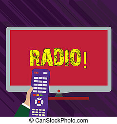 Conceptual hand writing showing Radio. Business photo text Electronic equipment used for listening to broadcasts programs shows Hand Holding Remote Control infront of Wide Color PC Screen.