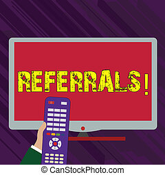 Conceptual hand writing showing Referrals. Business photo text Act of referring someone or something for consultation review Hand Holding Remote Control infront of Wide Color PC Screen.