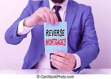 Conceptual hand writing showing Reverse Mortgages. Concept meaning borrower to access the unencumbered value of the property Man holds empty paper with copy space in front of him Space