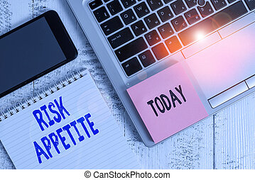 Conceptual hand writing showing Risk Appetite. Business photo showcasing the level of risk an organization is prepared to accept Laptop ruled notepad smartphone sticky note on wooden table.