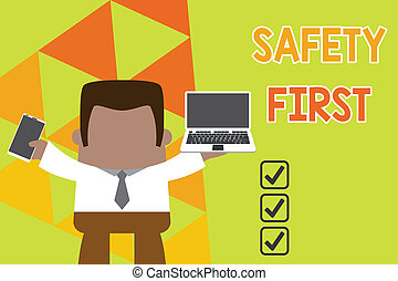 Conceptual hand writing showing Safety First. Business photo text used to say that the most important thing is to be safe Professional man holding laptop in left mobile phone right.