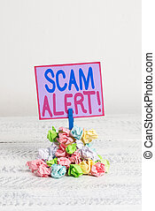 Conceptual hand writing showing Scam Alert. Business photo text fraudulently obtain money from victim by persuading him Reminder pile colored crumpled paper clothespin wooden space.