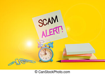 Conceptual hand writing showing Scam Alert. Business photo text fraudulently obtain money from victim by persuading him Alarm clock pencil clips note stacked notepads colored background.