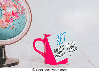 Conceptual hand writing showing Set Smart Goals. Business photo showcasing giving criteria to guide in the setting of objectives Globe map coffee cup sticky note lying vintage wooden table.