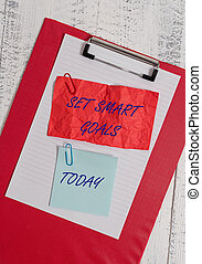 Conceptual hand writing showing Set Smart Goals. Concept meaning giving criteria to guide in the setting of objectives Clipboard paper crushed sticky note clip wooden background
