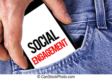Conceptual hand writing showing Social Engagement. Business photo showcasing post gets high reach Likes Ads SEO Advertising Marketing written on Mobile phone holding by man the Jeans background.