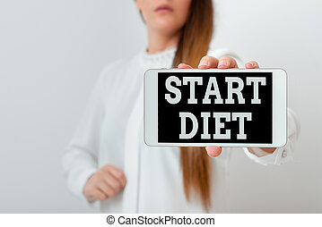 Conceptual hand writing showing Start Diet. Business photo showcasing the practice of eating food in a regulated and supervised fashion Model displaying black screen modern smartphone mock-up.