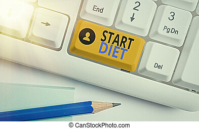 Conceptual hand writing showing Start Diet. Business photo text the practice of eating food in a regulated and supervised fashion Colored keyboard key with accessories arranged on empty copy space.