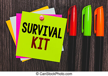 Conceptual hand writing showing Survival Kit. Business photo showcasing Emergency Equipment Collection of items to help someone Paper notes Communicate ideas Markers Wooden background.
