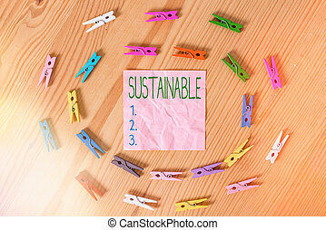 Conceptual hand writing showing Sustainable. Concept meaning the ability to be sustained, supported, upheld, or confirmed Colored crumpled papers wooden floor background clothespin
