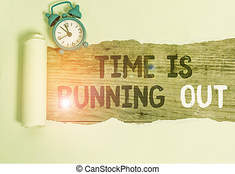 Conceptual hand writing showing Time Is Running Out. Business photo text Deadline is approaching Urgency things cannot wait Alarm clock and torn cardboard on a wooden classic table backdrop.