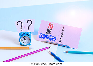 Conceptual hand writing showing To Be Continued. Business photo text indicate that the story continues in the next episode Mini size alarm clock beside stationary on pastel backdrop.