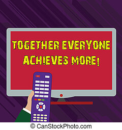Conceptual hand writing showing Together Everyone Achieves More. Business photo text Members create synergy strong sense commitment Hand Holding Remote Control infront of Wide Color PC Screen.