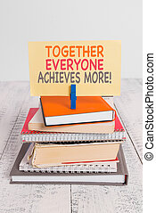 Conceptual hand writing showing Together Everyone Achieves More. Business photo text Members create synergy with strong sense mutual commitment pile stacked books notebook pin color reminder white wooden.