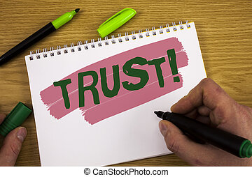 Conceptual hand writing showing Trust Motivational Call. Business photo text Belief in the Reliability Truth Ability Confidence written by Man on Notepad holding Marker on wooden background Pen.