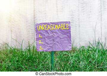 Conceptual hand writing showing Unreasonable. Concept meaning not conformable to reason or exceeding the bounds of reason Plain paper attached to stick and placed in the grassy land