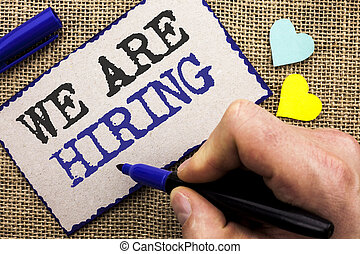 Conceptual hand writing showing We Are Hiring. Business photo showcasing Talent Hunting Job Position Wanted Workforce HR Recruitment written on Sticky Note on the jute background with Love Hearts.