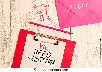 Conceptual hand writing showing We Need Volunteers. Business photo showcasing someone who does work without being paid for it Colored clipboard paper sheet pencil clips wooden background.