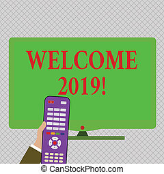 Conceptual hand writing showing Welcome 2019. Concept meaning instance or analysisners of greeting someone like new year Hand Holding Remote Control infront of Wide Color PC Screen