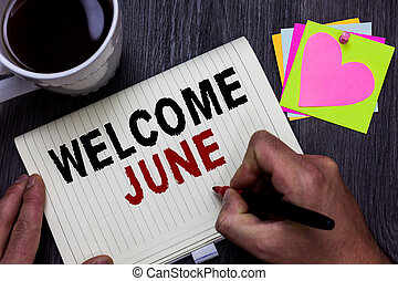 Conceptual hand writing showing Welcome June. Business photo text Calendar Sixth Month Second Quarter Thirty days Greetings Man holding marker giving ideas wooden table cup coffee hearts.