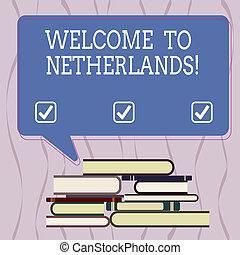 Conceptual hand writing showing Welcome To Netherlands. Business photo text Warm greeting to the visitors of Netherlands Uneven Pile of Hardbound Books and Rectangular Speech Bubble.