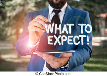 Conceptual hand writing showing What To Expect. Business photo showcasing asking about regard something as likely to happen occur Businessman in blue suite stands with mobile phone in hands.