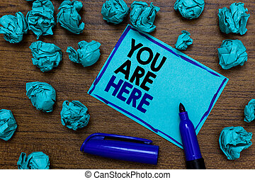 Conceptual hand writing showing You Are Here. Business photo showcasing This is your location reference point global positioning system written blue letters on page blue marker and paper lumps.