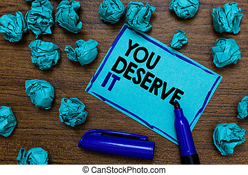Conceptual hand writing showing You Deserve It. Business photo showcasing Reward for something well done Deserve Recognition award written blue letters on page blue marker and paper lumps.