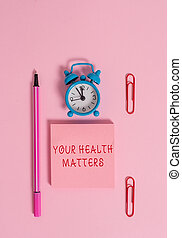 Conceptual hand writing showing Your Health Matters. Business photo text good health is most important among other things Metal alarm clock blank notepad marker clips colored background.
