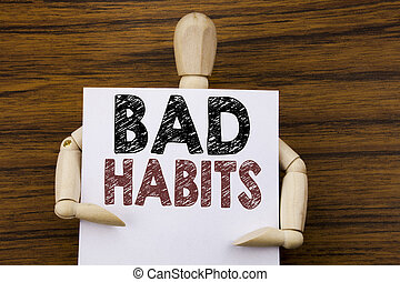 Conceptual hand writing text caption inspiration showing Bad Habits. Business concept for Improvement Break Habitual Hebit written on sticky note paper on the wooden background. Holding by the sculpture.